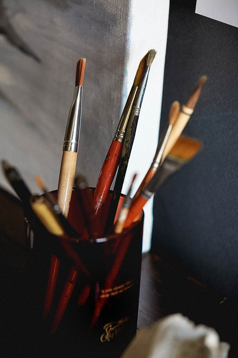 A glass candle jar with paintbrushes