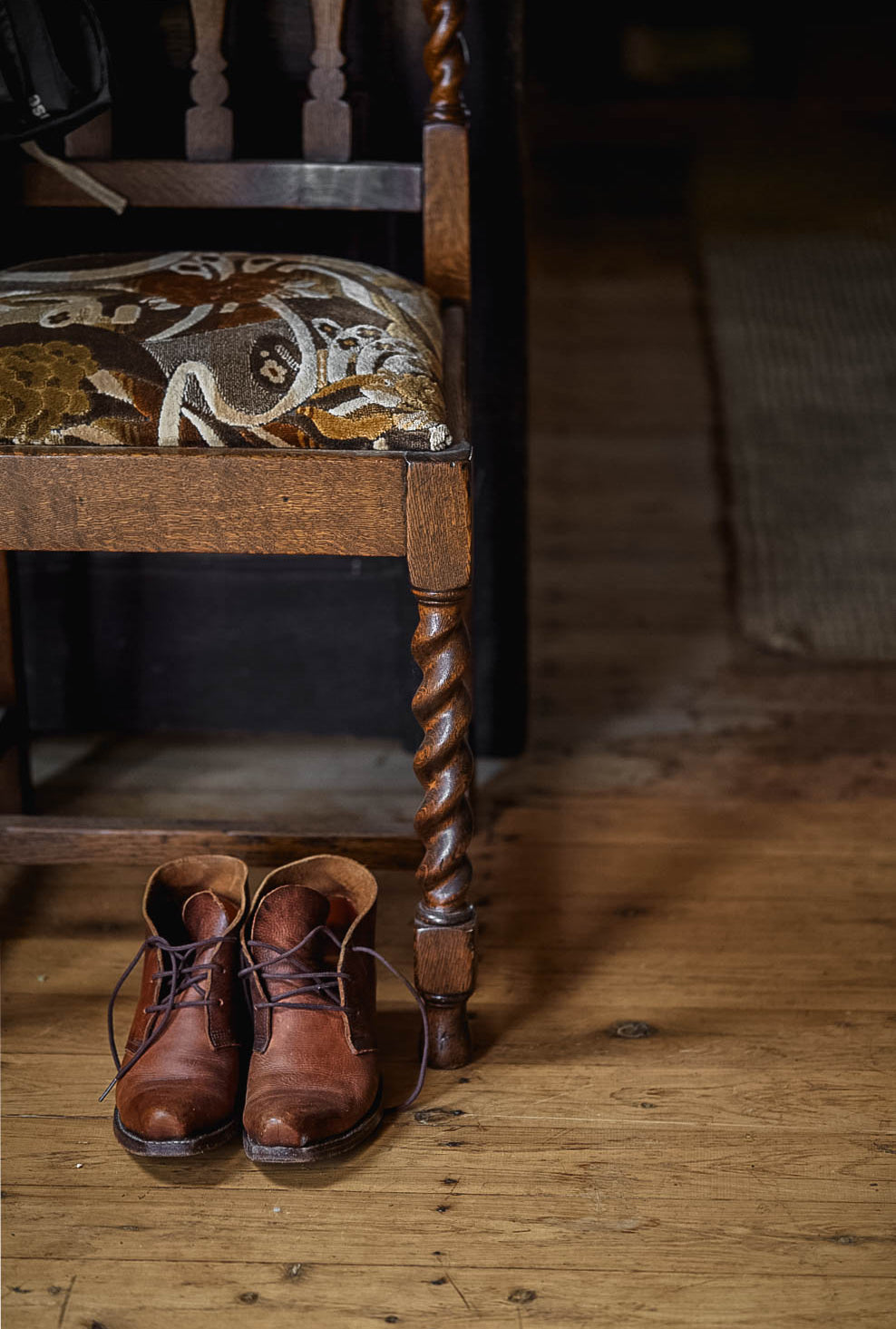 An antique wooden chair with a velvet seat and pair of handmade cowboy boots underneath