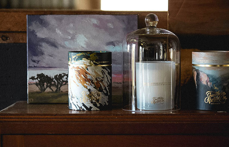 Scented candles and a painting by Rowena Dean rest on a vintage sideboard.