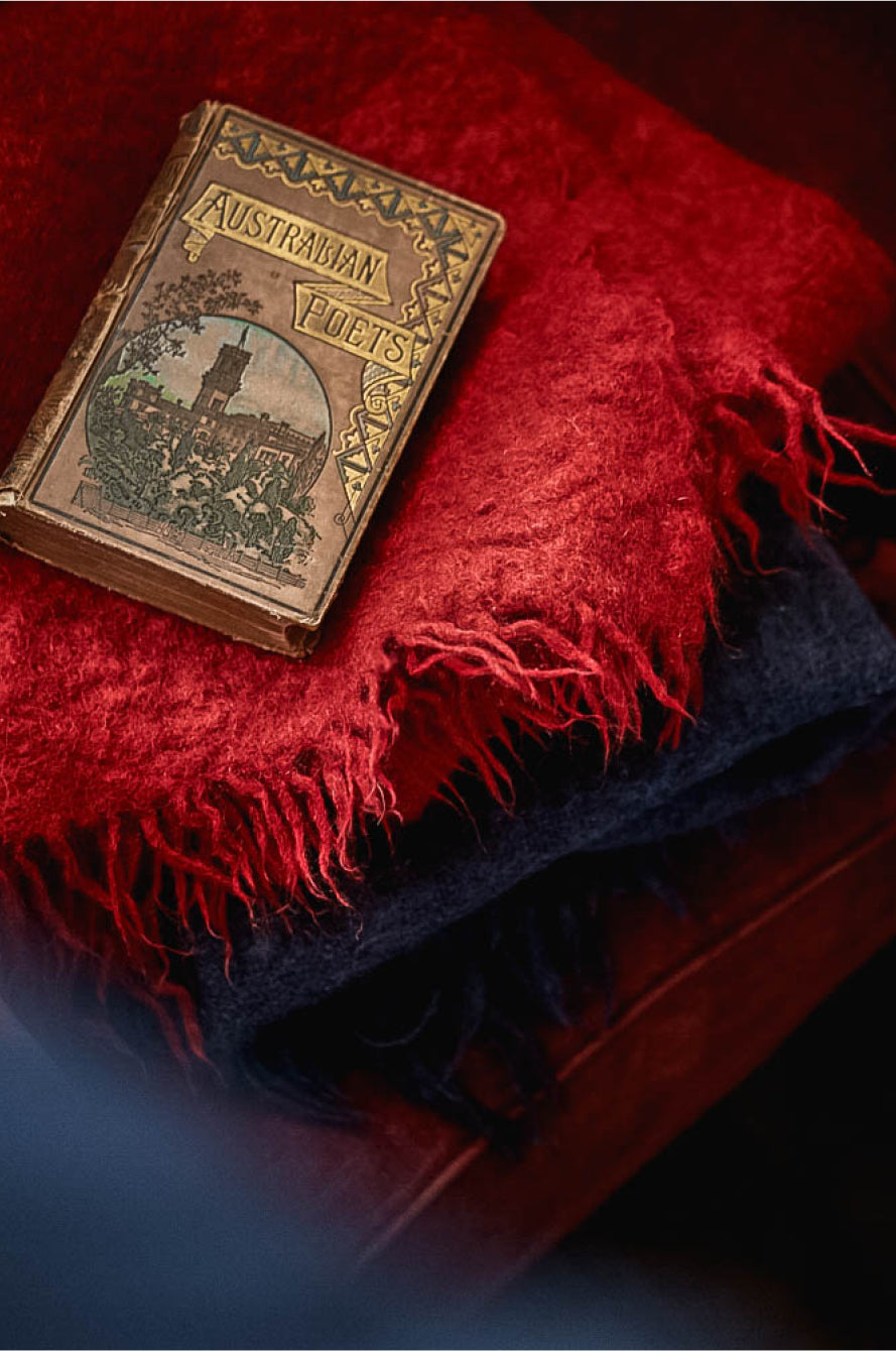 A vintage book of Australian poetry on a red mohair blanket