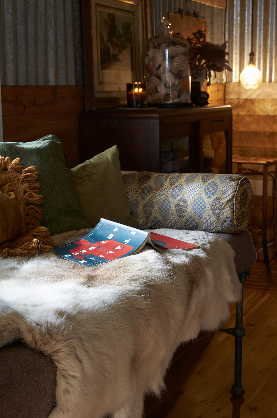 An open book on a vintage shearer's bed featuring an ethically sourced deer skin, antique bookcase and candles
