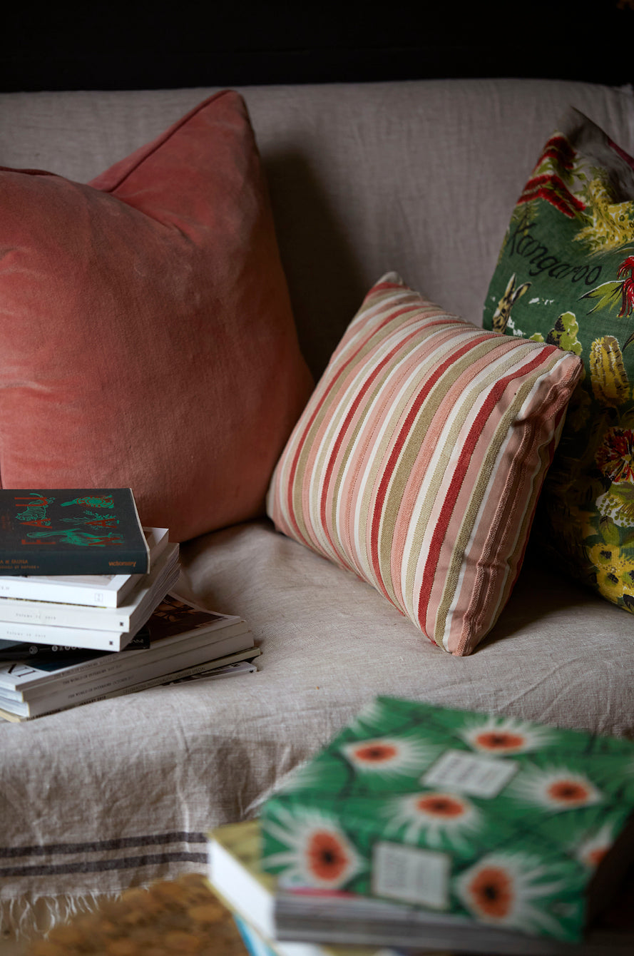 Books and magazines piled onto a comfy sofa with velvet cushions in green and pink colours