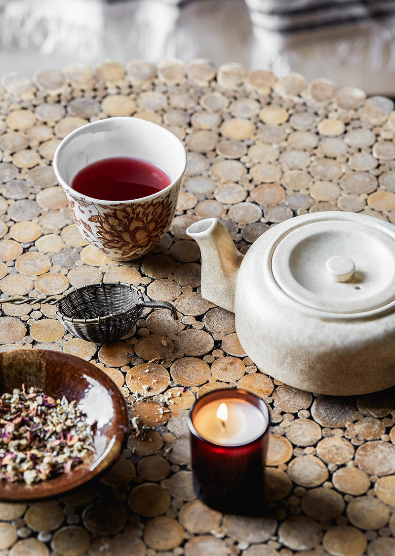 A table setting with a vintage teapot, herbal tea and Southern Wild Co scented candle