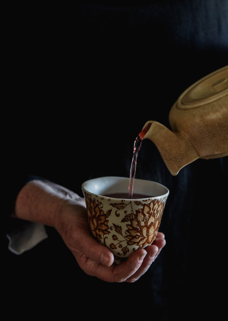 A hand holding a teacup, pouring herbal tea from a vintage teapot at Southern Wild Co