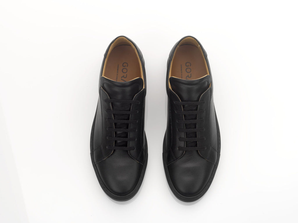 black leather sneakers with black rubber soles