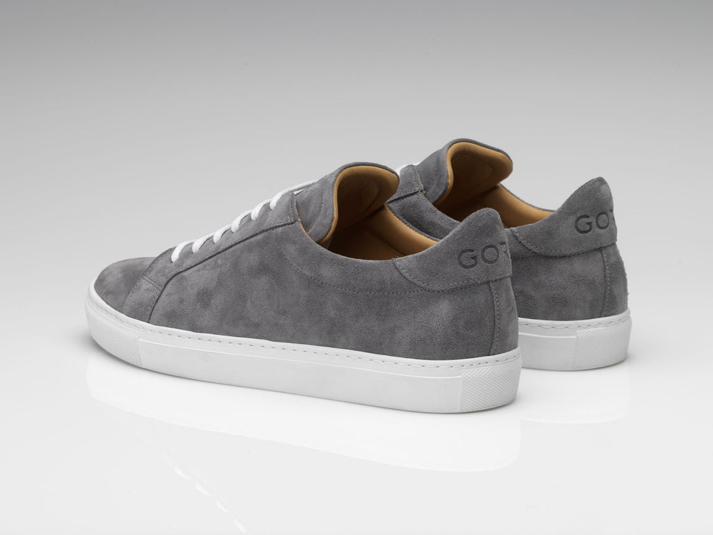 grey suede sneakers with white rubber soles