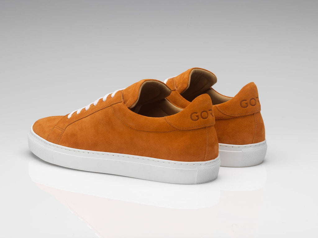 orange suede sneakers with white rubber soles
