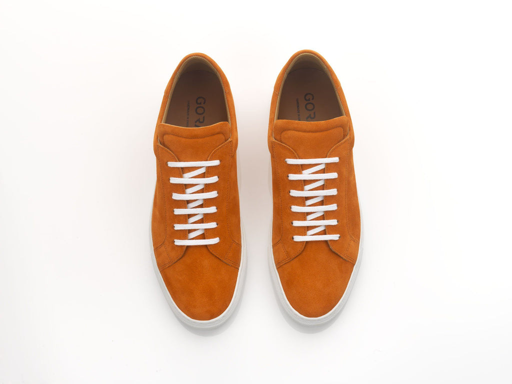 orange sneakers with white rubber soles
