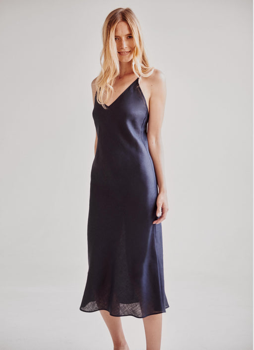 Model wearing Navy 100% linen slip dress with adjustable straps.