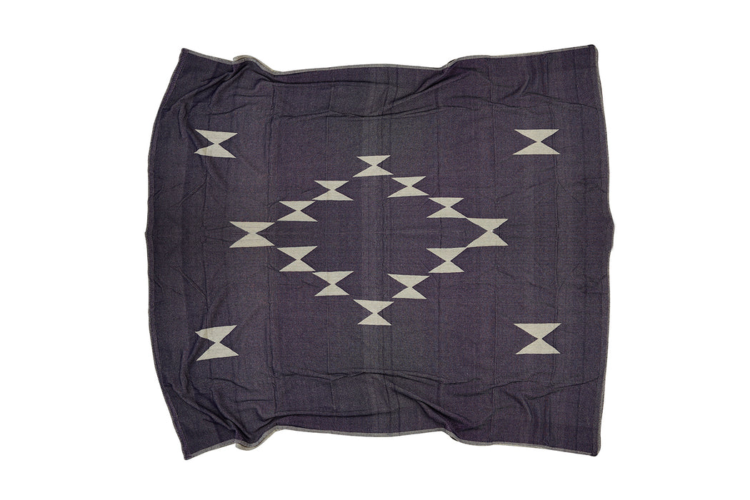 Double-sided bed blanket with woven jacquard pattern with blanket stitch edge detail.