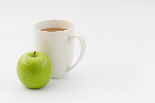 cup of coffee in a white coffee mug with a green apple