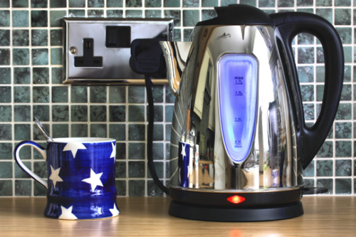 stainless steel electric kettle with a blue star mug beside it waiting to be filled