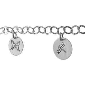 Sterling silver charm bracelet close-up photo.  Showcasing dragonfly and butterfly symbols.