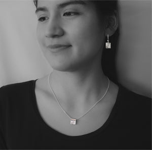 Sterling silver square earrings and necklace with Canadian symbols on black and white model photograph.