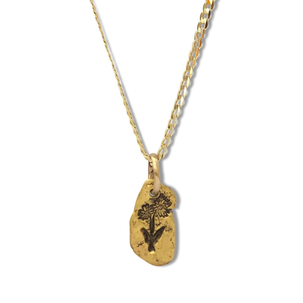 Gold nugget Arnica (northern daisy) pendant on 10 karat gold chain.