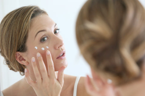 woman applying cream to her face in front of mirror