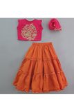 Hot pink embroidered choli and rusty orange tiered lehenga with dupatta