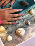 Nails with shells and glitter and gems following assessment on nail services course
