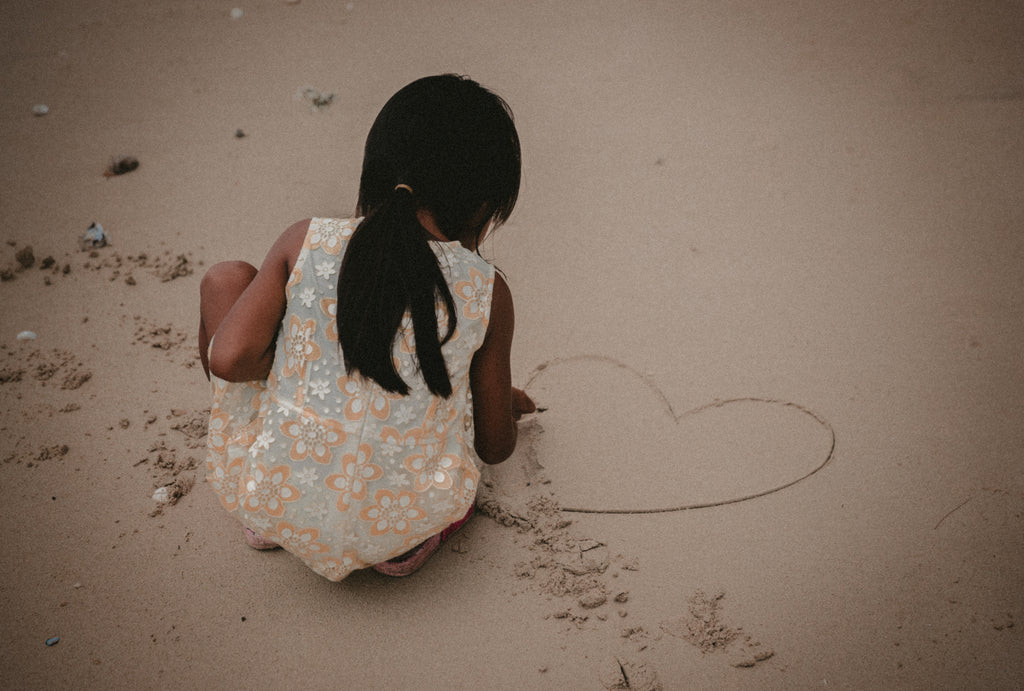 Little girl drawing a heart in the sand at the beach