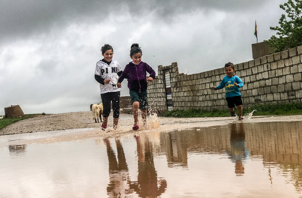 Kids playing at a beach running through a puddle