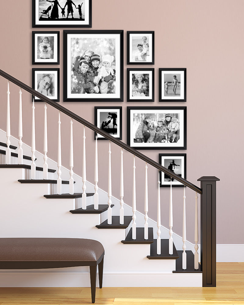 A Gallery Wall of Family Photos Printed in Black & White in Stairway