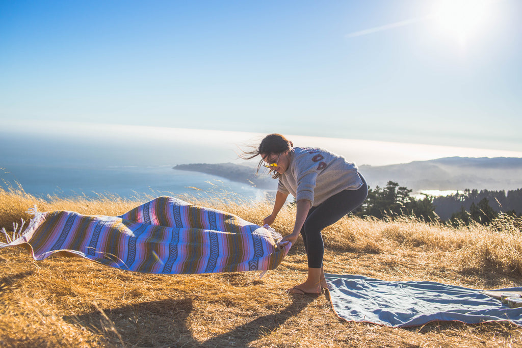 Candid photo of woman laying out a blanket in the wind with the ocean in the background