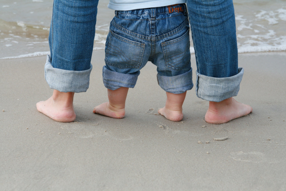 Close-up beach photo of adult and baby feet together in the sand