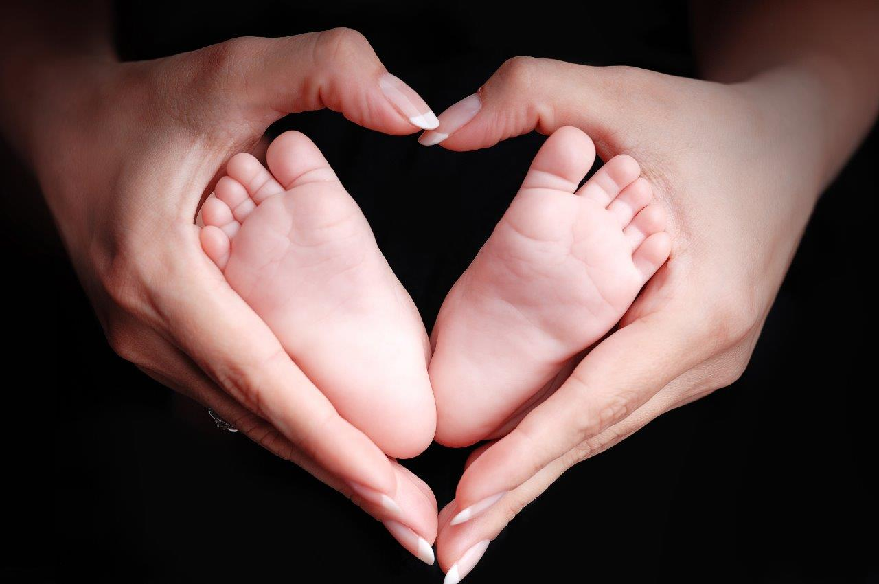 Mother's hands framing baby's feet in the shape of a heart