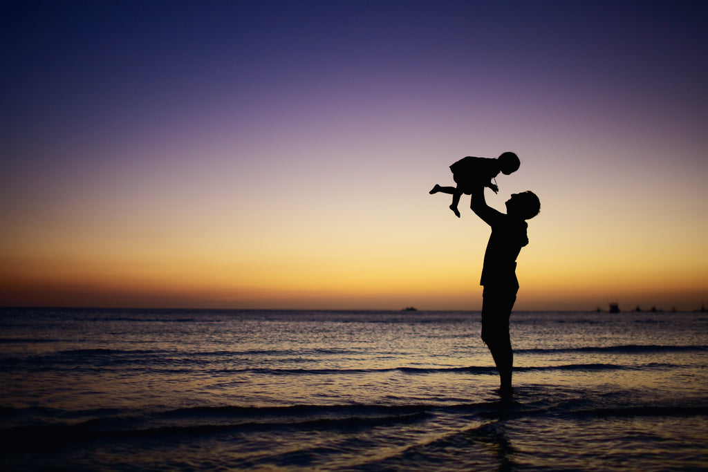 Silhouette of adult and child at the beach at sunset