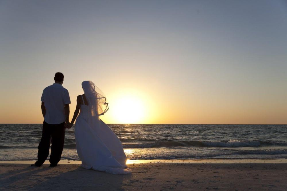 Using leading lines in wedding photography - photo of a bride and groom on the beach at sunset