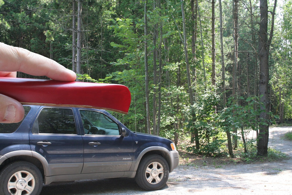 Forced Perspective photo of a person holding a canoe that looks miniature