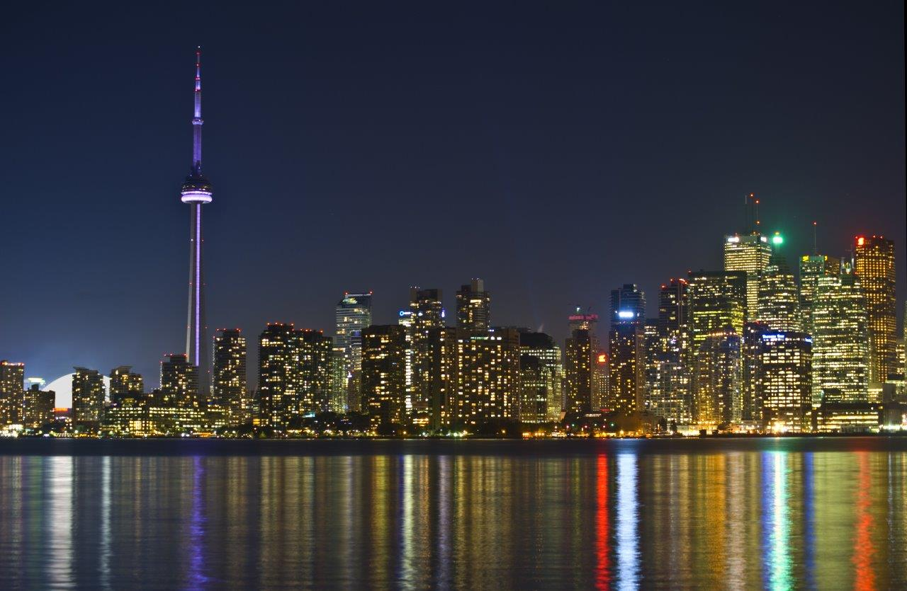 View of CN Tower at night with lights reflecting off water