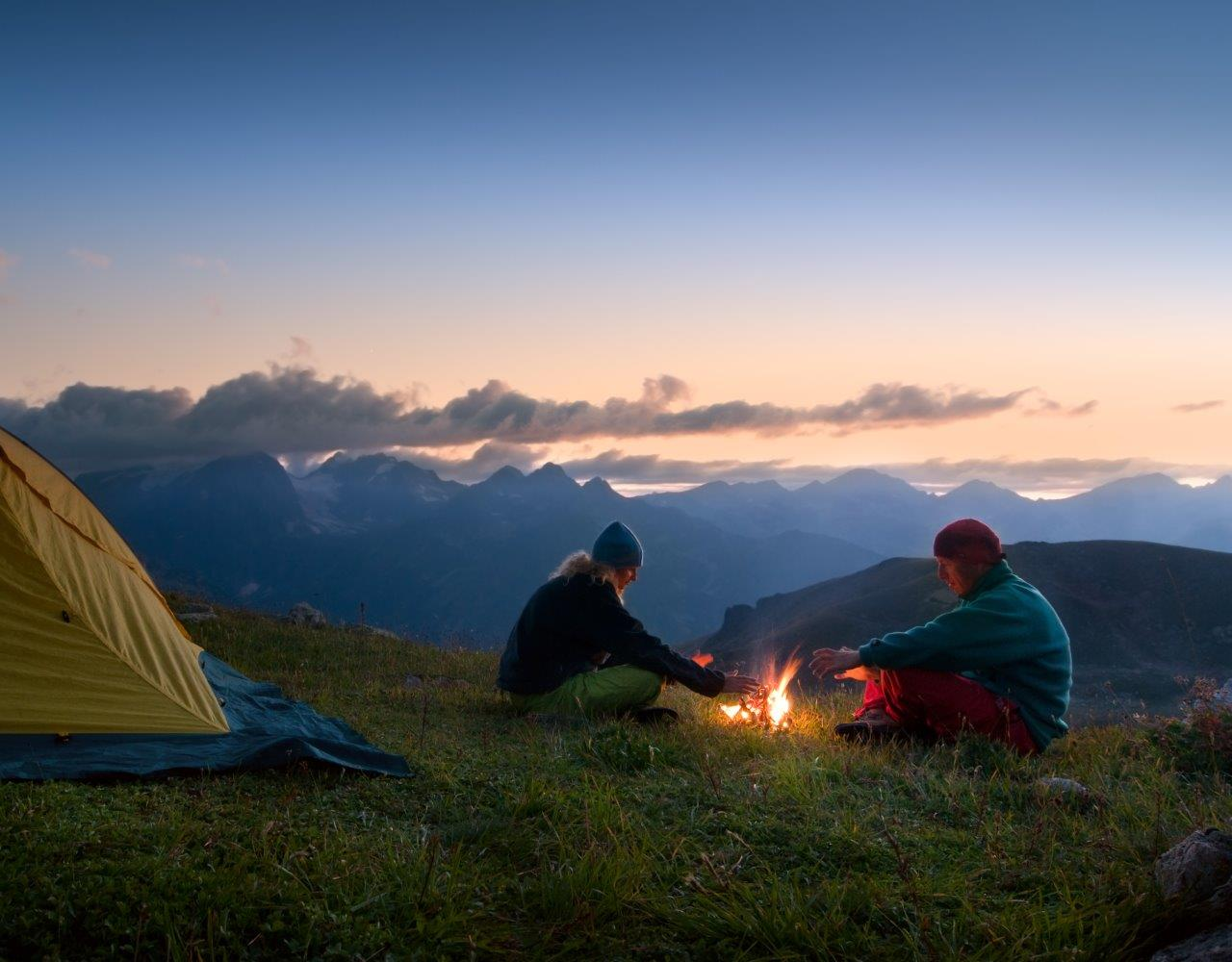Two people tent camping in the mountains at night with a campfire