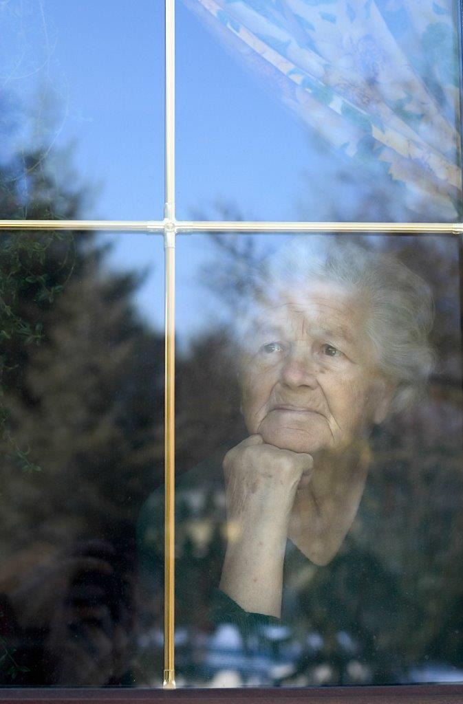 Elderly woman thoughtfully looking out a window