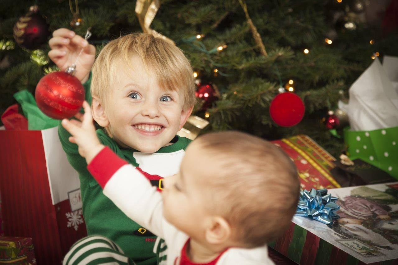 Holiday photo of an excited little boy holding a Christmas decoration away from his little sister