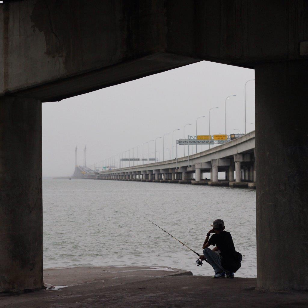 Person fishing under a bridge on an overcast day, an example of creative compositional framing