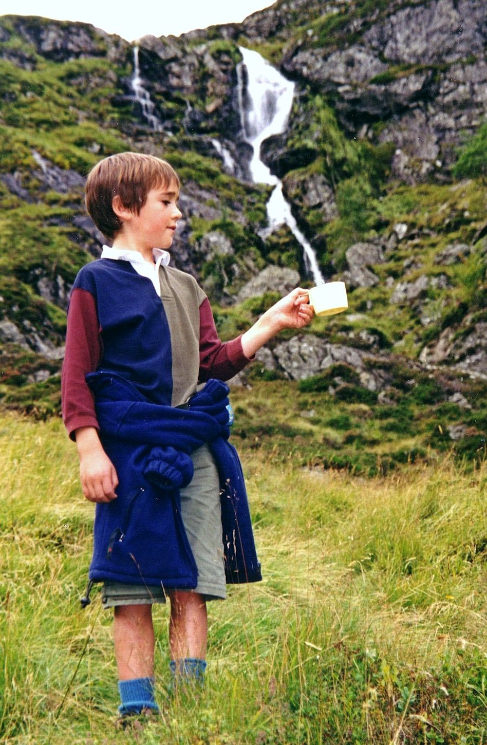 Forced perspective photo of a boy holding a cup with a waterfall pouring into it