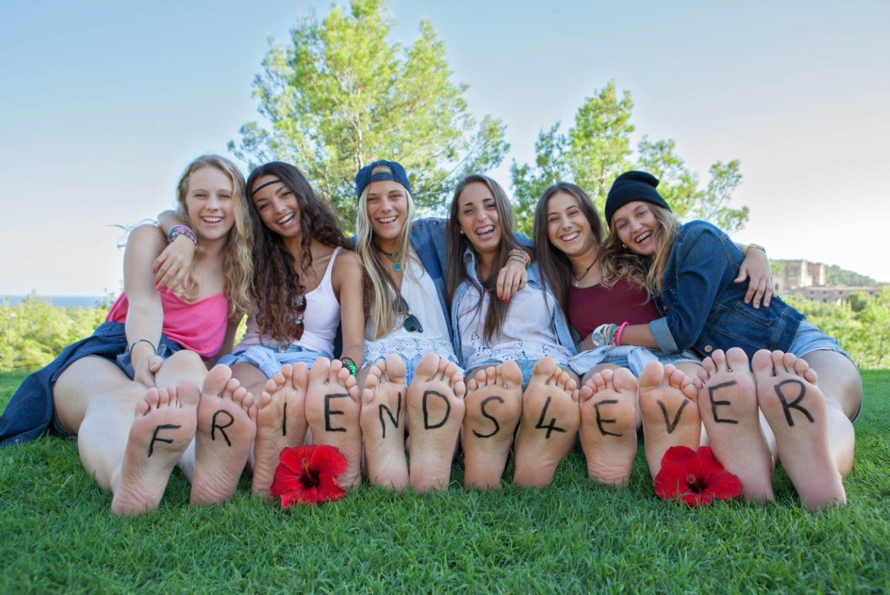 "Outdoor group photo of girls with ""friends4ever"" written on their feet"