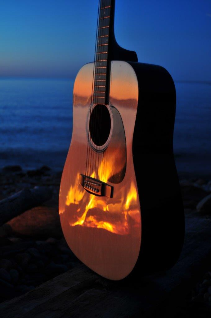 Acoustic guitar on the beach with reflection of campfire - example of low-light photography
