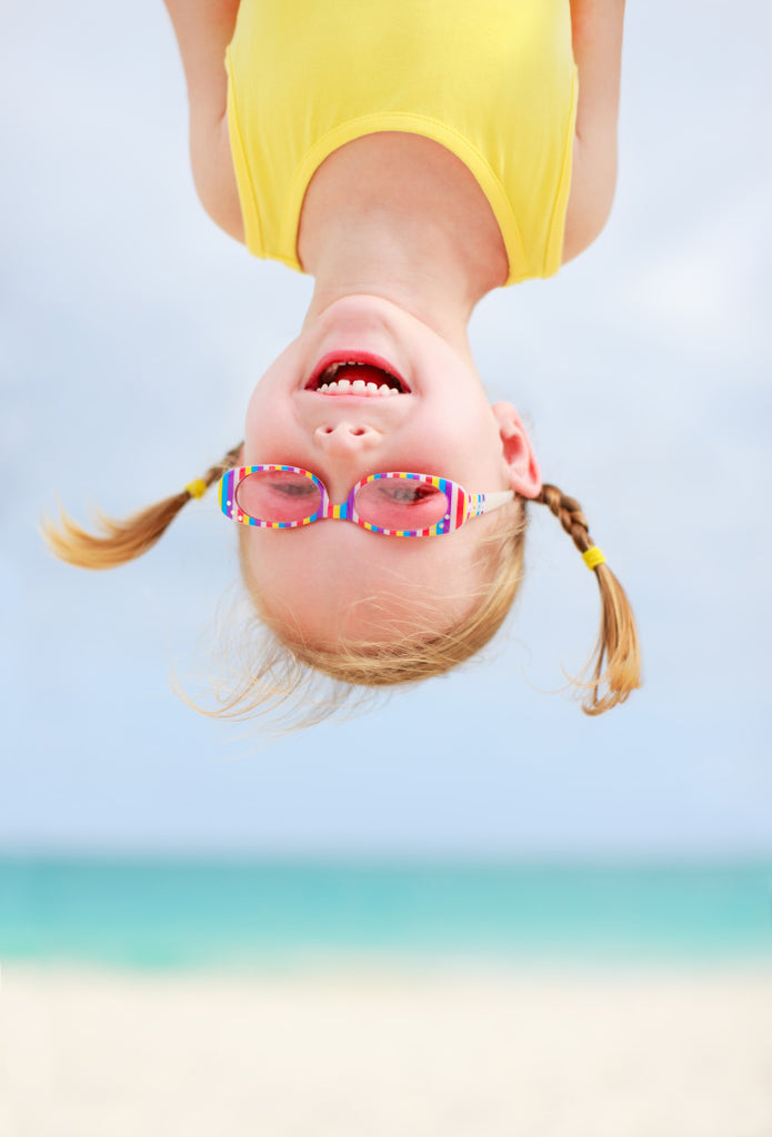 Happy little girl hanging upside-down at the beach with ocean in the background