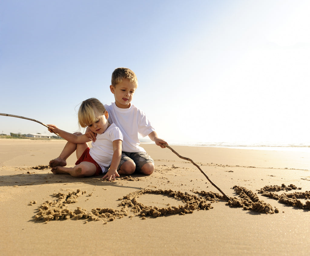 Beach photo of children writing the word love in the sand