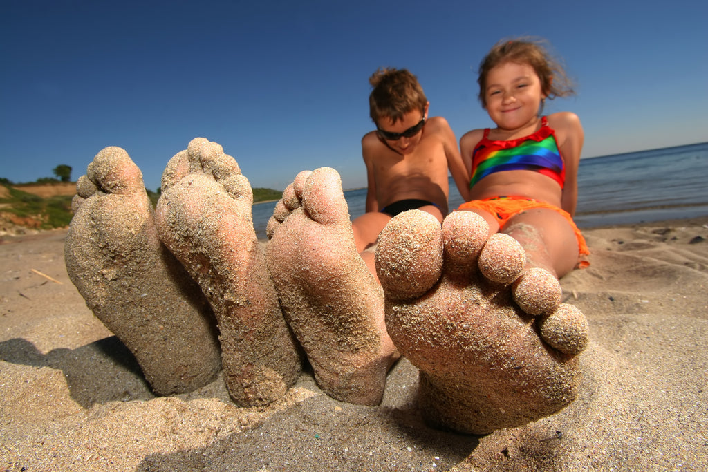 Kids on the beach with sandy feet