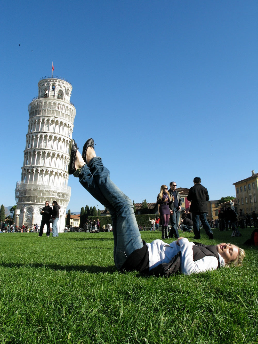 Forced perspective photo of a person holding up the Leaning Tower of Pisa with their legs