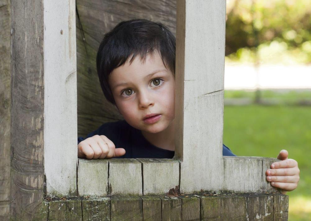 Little boy looking through a wood-framed window as an example of compositional framing