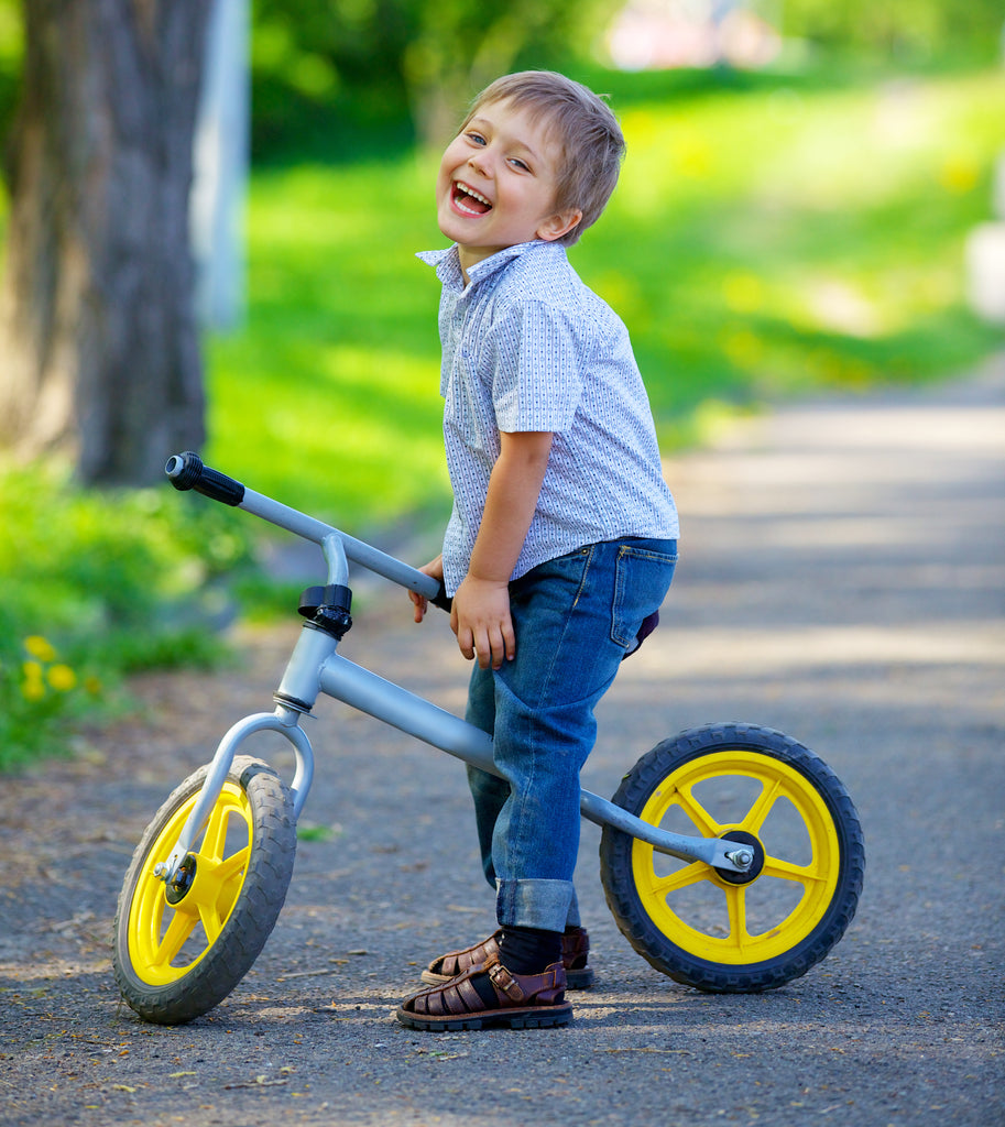 Happy little boy on a two-wheel bicycle with shallow depth of field