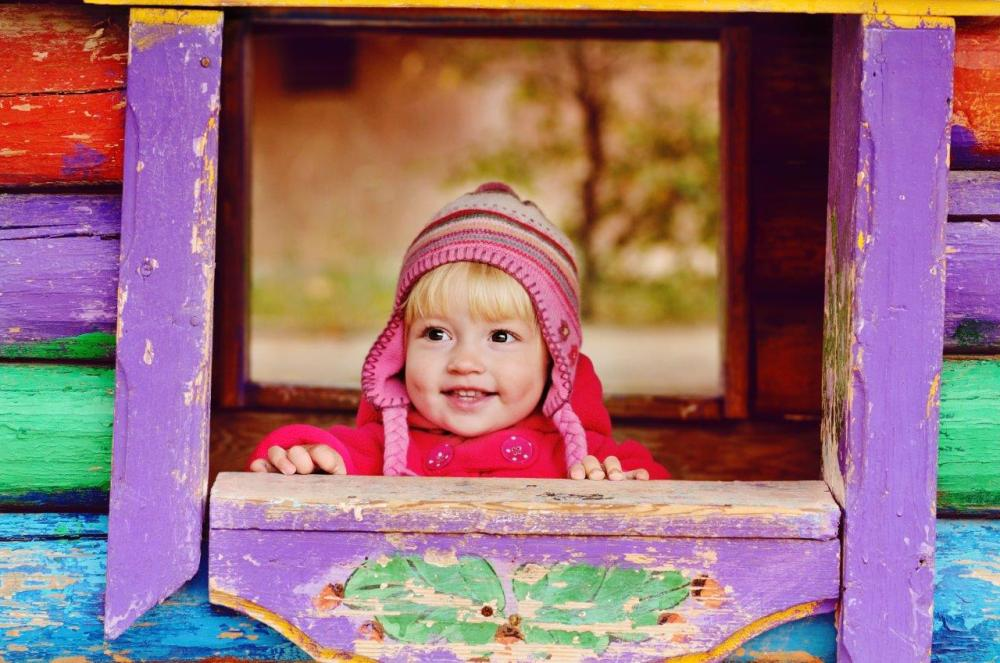 Little girl in a colourful playhouse as an example of creative compositional framing