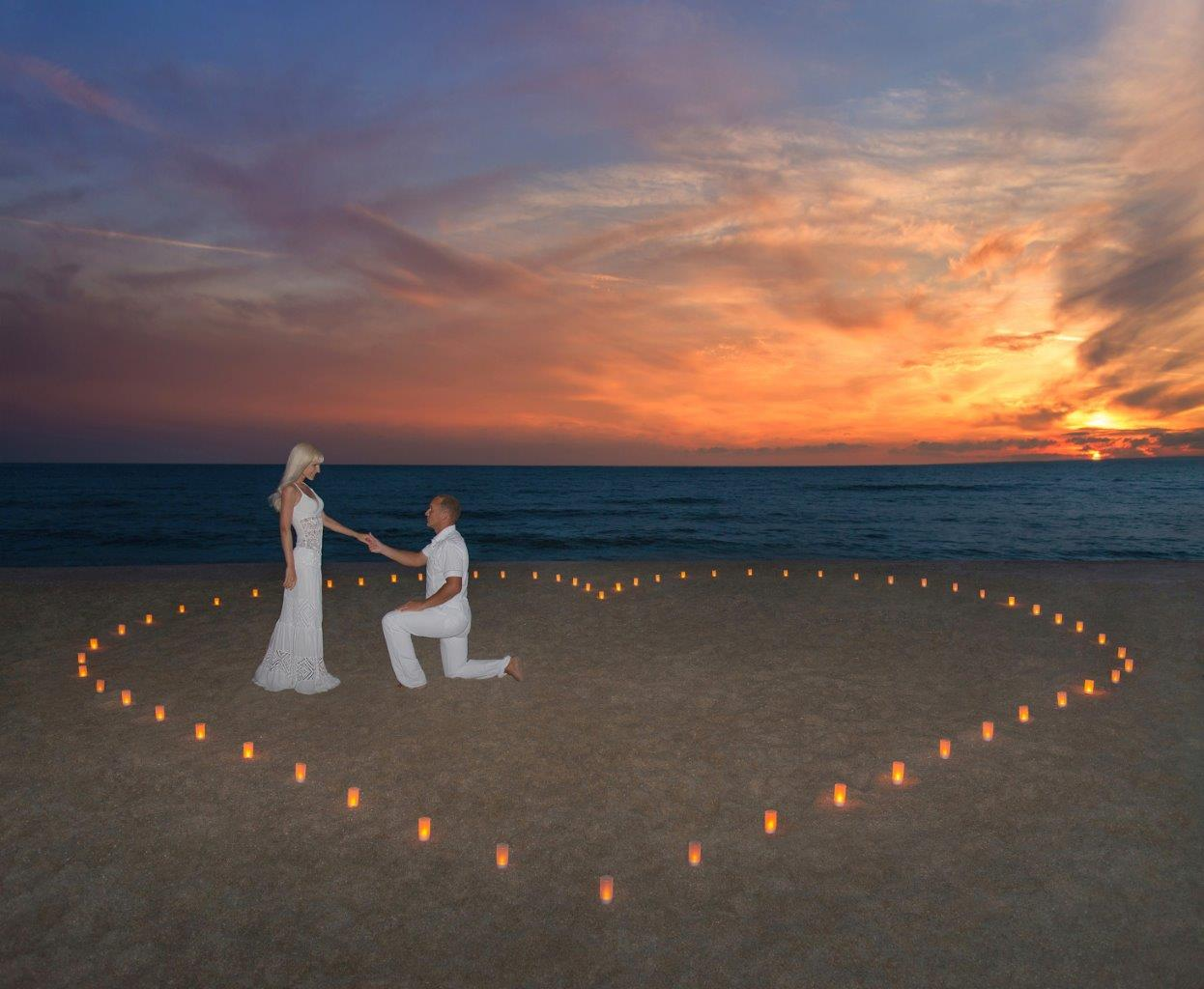 Man proposing to woman at sunset with candles arranged in the shape of a heart