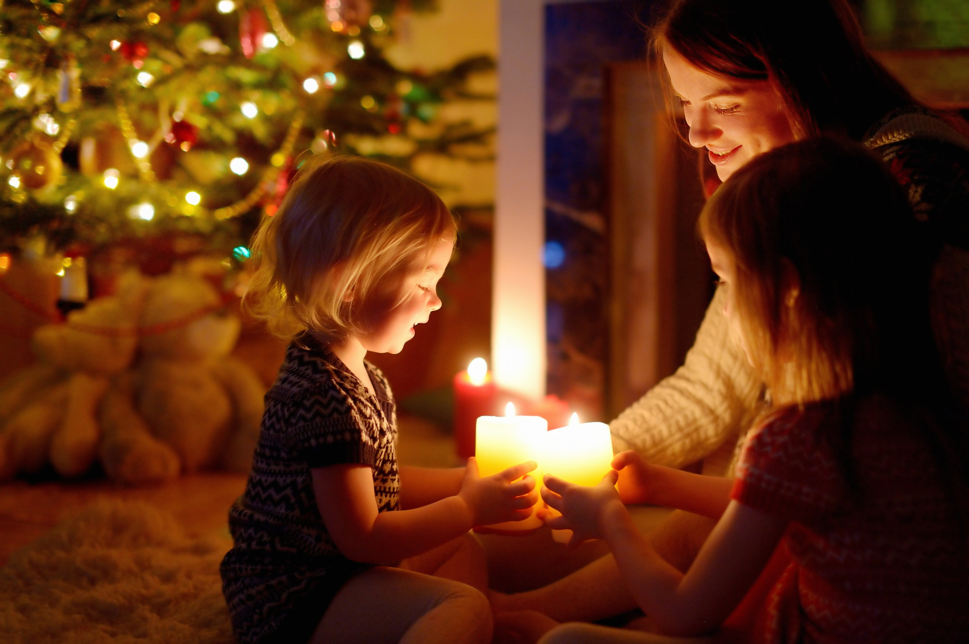 Woman and children holding lit candles in front of the Christmas tree at night - holiday photography example
