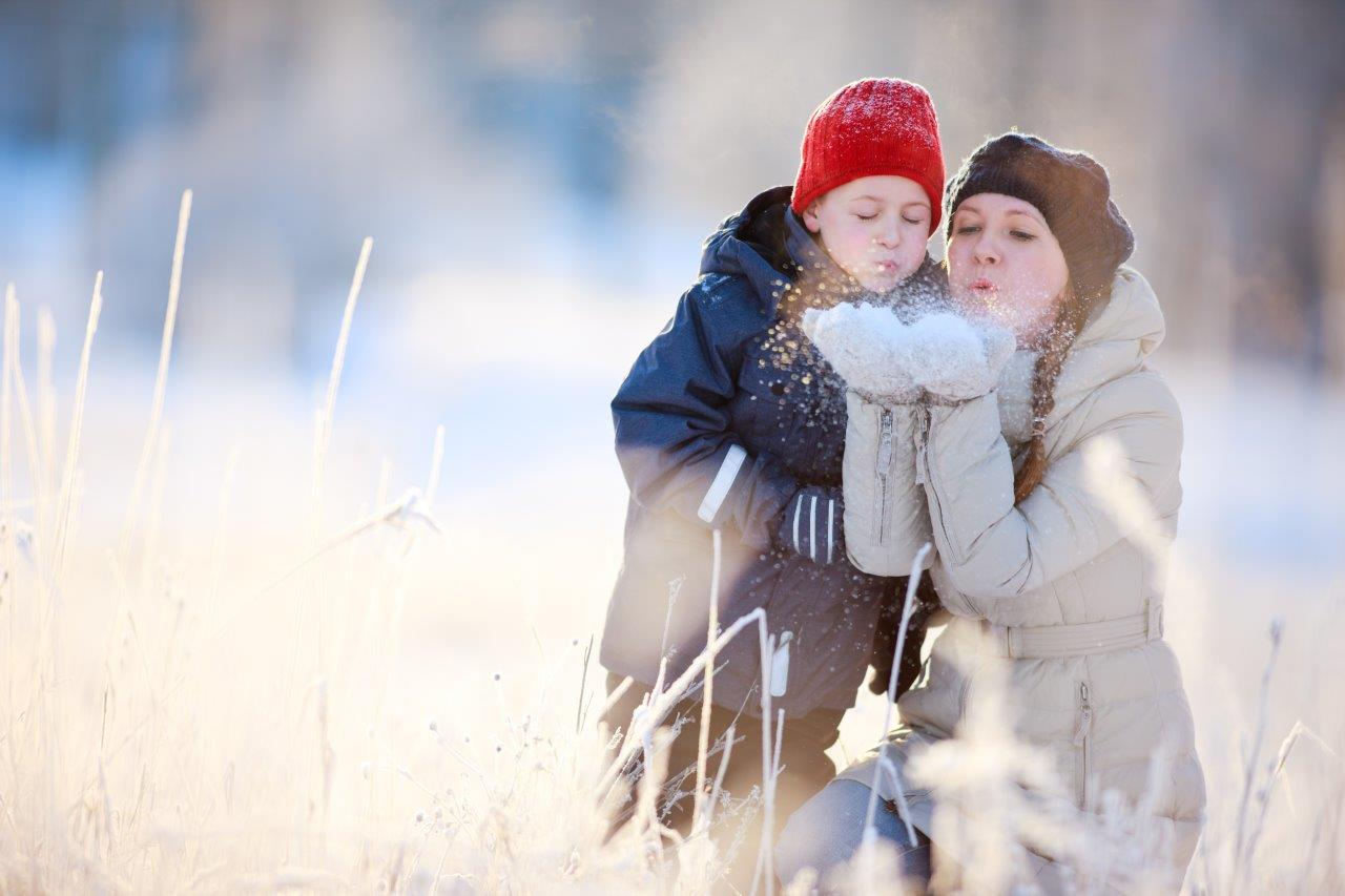 Holiday photo of a mother and child outside blowing snow from their mittens