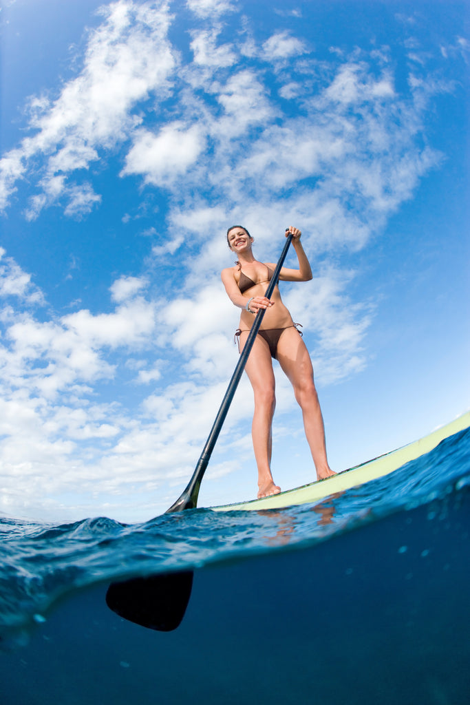 Underwater photo of a woman on a stand-up paddle board